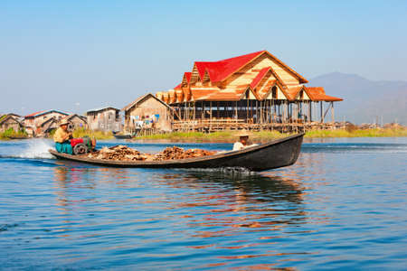Inle Lake, Myanmar - January 04, 2007: Local Burmese people traveling by motor long-tail boat to traditional fishers village with stilt houses near Nyaungshwe Township on Inle lake, Shan state.