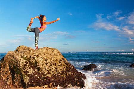 Meditación en el cielo del atardecer de fondo. Jóvenes activos mujer de pie en pose de yoga en la playa de roca para mantener el ajuste y la salud. Estilo de vida saludable, fitness al aire libre, actividad deportiva en las vacaciones de verano de la familia. Foto de archivo - 85107340