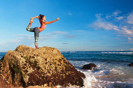 Meditation on sunset sky background. Young active woman stand in yoga pose on beach rock to keep fit and health. Healthy lifestyle, outdoor fitness, sport activity on summer family holiday.
