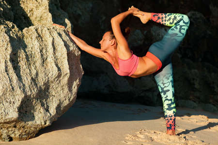 Meditation on rock background. Young active woman stand in yoga pose on beach rock, stretching to keep fit and health. Healthy lifestyle, outdoor fitness, sports activity on summer family holiday. 版權商用圖片