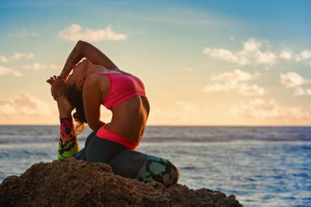 Meditation on sunset sky background. Young active woman sit in yoga pose on beach rock, stretching to keep fit and health. Healthy lifestyle, outdoor fitness, sports activity on summer family holiday. 版權商用圖片