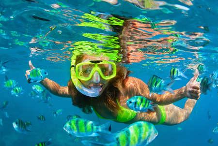 Gelukkige familie - meisje in snorkelen masker duiken met tropische vissen in koraalrif zee zwembad. Reis lifestyle, watersport buitenavontuur, onderwater zwemmen op zomervakantie vakantie met kinderen. Stockfoto