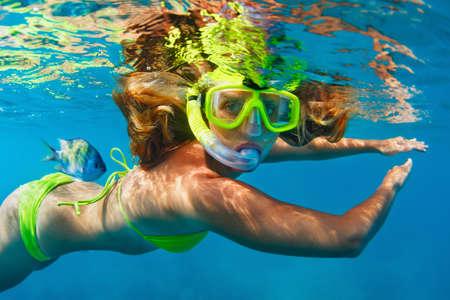 幸せな家族 - シュノーケ リング マスクの女の子はサンゴ礁の海水プールで熱帯の魚とダイビングします。水スポーツの屋外の冒険は、水中水泳の子