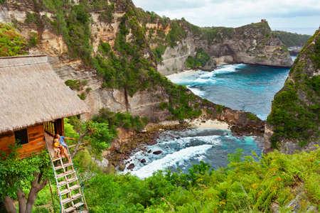 Gelukkige familie reizen levensstijl. Moeder met kind zit op stappen van traditioneel huis op boom, kijk naar Atun strand, Nusa Penida eiland. Populaire reisbestemming op Bali vakantie. Indonesische achtergrond. Stockfoto