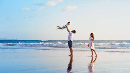 행복한 가족 휴가. 즐거운 아버지, 어머니, 아기 아들 일몰의 가장자리를 따라 재미와 함께 산책 바다 서핑 검은 모래 해변에. 활동적인 부모와 어린이 스톡 콘텐츠