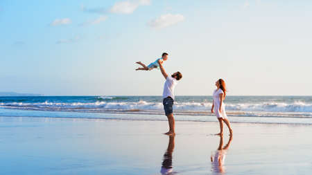 Happy family holidays. Joyful father, mother, baby son walk with fun along edge of sunset sea surf on black sand beach. Active parents and people outdoor activity on summer vacations with children. Stock Photo