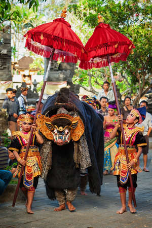 Bali, Indonesia - June 21, 2015: Dancers in ethnic costumes walk under umbrellas with men in traditional mask of Balinese good spirit Barong on hindu ceremony Ngelawang during temple festival.