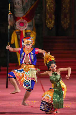 Denpasar Bali island, Indonesia - June 25, 2015: Beautiful Balinese woman and man in ethnic dancer costume, dancing traditional temple dance at art and culture festival parade. Editorial