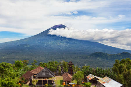 View from Lempuyang mountain to traditional Balinese temple on Mount Agung slopes background. Mount Agung is popular tourist hiking route and highest active volcano on Bali island, Indonesia.
