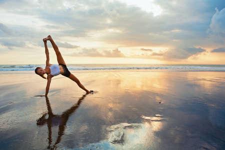 Meditatie op zonsondergang hemelachtergrond. De jonge actieve vrouw in yoga stelt op overzees strand, zich uitrekt om geschikt en gezondheid te houden. Gezonde levensstijl, outdoor fitness, sportactiviteit op zomervakantie. Stockfoto