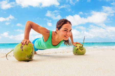 Active woman doing fitness exercise plank on coconut to keep fit and health. Beach surf background. Healthy lifestyle, morning workout, sport activity on summer family vacation in tropical island. Imagens