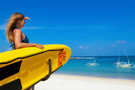 Life saving yellow board with surf rescue sign. Young lifeguard woman stand on duty, look at blue sea. Assure swimming people safety. Summer family vacation on ocean beach. Travel background.