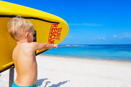 Life saving yellow board with surf rescue sign. Funny children lifeguard stand on duty, look at blue sea. Assure swimming people safety. Summer family vacation on ocean beach. Travel background. Stock Photo
