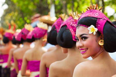 Denpasar, Bali island, Indonesia - June 10, 2017:  Group of beautiful women in traditional Balinese costumes carry religious offering for hindu ceremony on street parade at art and culture festival.