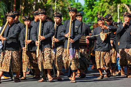 Denpasar, Bali island, Indonesia - June 10, 2017:  Group of Balinese people in traditional costumes. Musician men playing music on bamboo flute on street parade at art and culture festival.