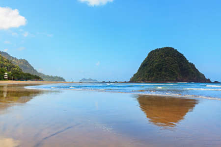 View of Red island beach ( pantai Pulau merah ) in Banyuwangi in Indonesia. Walking along sea surf by empty of people endless sand beach. Java popular travel destination. Summer holiday background. Stock Photo