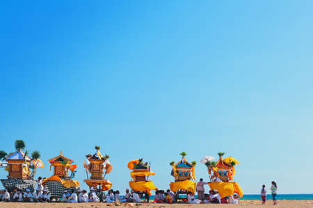 Bali Island, Indonesia - March 18, 2015: Balinese people procession rest after walking with hindu shrines to beach for traditional water purifying ceremony Melasti before celebration silence day Nyepi
