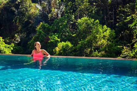 Beautiful tanned woman on summer beach holiday relaxing in luxury spa hotel in infinity swimming pool with tropical jungle view. Healthy lifestyle, family travel background. Bali island tour. Imagens