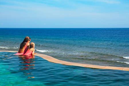 Happy family. Mother, baby daughter relax in luxury spa resort at poolside in infinity swimming pool with sea view. Travel lifestyle, recreation on summer beach vacation, kids water sports activity.