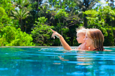Happy family - mother, baby son learn to swim. Joyful kid has fun in luxury resort swimming pool. Travel lifestyle at summer beach vacation, children water sports activity, swimming lesson with parent