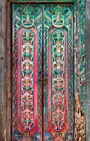 Old teak wood door with traditional carving in a Balinese temple decorated ornaments and people figures. Bali art backgrounds. Culture of indonesian people. Stock Photo - 91002957