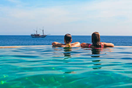 Happy young woman on summer beach holiday relaxing in luxury spa resort in infinity swimming pool with sea view. Healthy lifestyle, family travel background. Sailing yacht tropical island cruise.