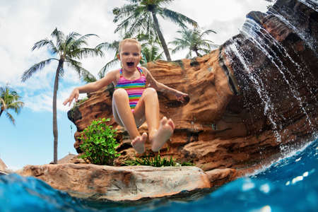 Funny child learn to swim with fun. Girl jumping high with splashes into water pool under waterfall. Healthy lifestyle, kids water sport activity, swimming lesson with parents on family beach vacation Stock Photo