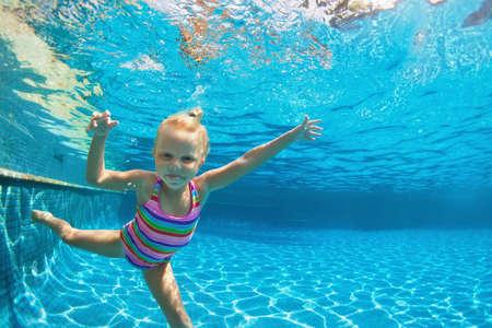 Het grappige portret van kind leert het zwemmen, duikend in blauwe pool met pret - diep onderwater het springen met plonsen. Gezonde gezinslevensstijl, kinderen watersportactiviteiten, zwemles met ouders. Stockfoto
