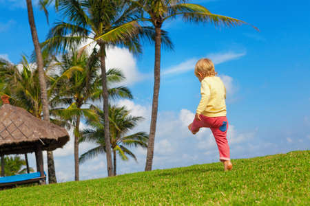 Happy child have fun at outside walk without parents. Active boy run and jump high by grass lawn in luxury resort garden. People activity on summer tropic holiday with kid. Family lifestyle background
