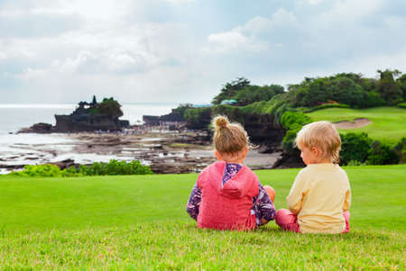 Happy kids at walk. Brother and sister sit on hill, look from high cliff at beach view, Balinese temple Tanah lot. Leisure activity on summer tropic holiday with child on Bali. Family travel lifestyle Stock Photo