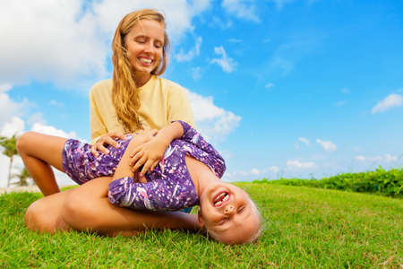 Happy family on green grass lawn. Child have fun on outside walk - mother tickling funny baby son lying on her laps. Active people activity on tropical holiday with kid. Summer lifestyle background.