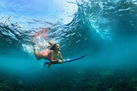 アクションでのビキニでアクティブな女の子。ボード サーフィン、ダイビング、水中破壊の大きな波を受けるとサーファーの女性。10 代のライフ ス