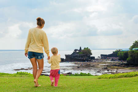 Happy child at walk with parent. Mother, baby son look from high cliff at beach, Balinese temple Tanah lot. People activity on summer tropic holiday with kid on Bali island. Family travel lifestyle.