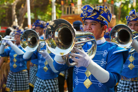DENPASAR, BALI ISLAND, INDONESIA - JUNE 13, 2015: Group of Balinese people. Men of brass band march on by city street and play music on parade at art and culture festival. Stock Photo - 91066437