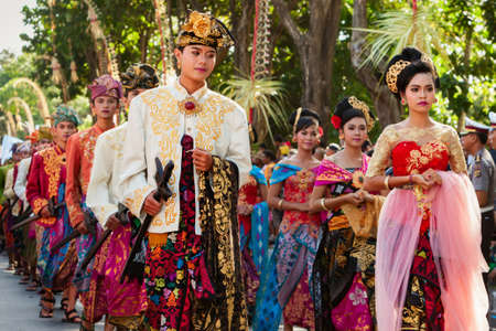 DENPASAR, BALI ISLAND, INDONESIA - JUNE 13, 2015: Group of beautiful women and men dancers in bright traditional costume. Balinese people dancing on street parade at art and culture festival. Editorial
