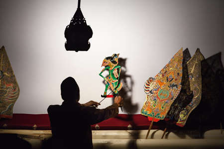 Jakarta, Java island, Indonesia - August 29, 2015: Black silhouette of indonesian puppeteer manipulating old traditional javanese shadow puppets Wayang Kulit.