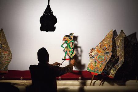 Jakarta, Java-eiland, Indonesië - Augustus 29, 2015: Zwart silhouet van Indonesische poppenspeler die oude traditionele Javaanse schaduwpoppetjes Wayang Kulit manipuleren.