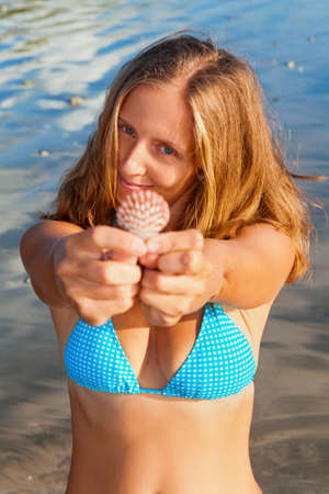 Happy family lifestyle. Young smiling woman in bikini hold in hands sea shell. Summer travel, leisure and recreational activities on tropical beach holiday with kids.