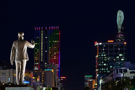 ホーチミン市、ベトナム - 9月 01, 2015: 夜の町の背景にホーチミン大統領の像.ネオンライトで照らされた近代的な建物やオフィスタワー。ホーチミン
