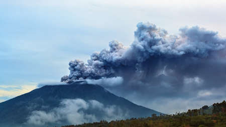 Monte Agung em erupção de pluma. Durante a erupção do vulcão, milhares de pessoas foram evacuadas da zona perigosa. Voos da companhia aérea para Bali foram cancelados, aeroporto de Denpasar fechado por causa das nuvens de cinzas vulcânicas Foto de archivo - 91630519