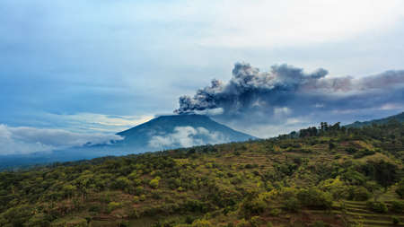 Mount Agung erupting plume. During volcano eruption thousands of people was evacuated from dangerous zone. Airline flights to Bali were canceled, Denpasar airport closed because of volcanic ash clouds Фото со стока