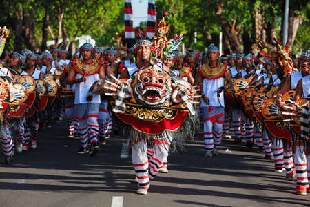 Denpasar, Bali island, Indonesia - June 10, 2017: Group of Balinese people. Musician men of baleganjur in traditional dance costumes with demon masks on street parade at art and culture festival.