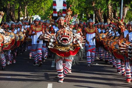 Denpasar, Insel Bali, Indonesien - 10. Juni 2017: Gruppe von Balinesen. Musiker von Baleganjur in traditionellen Tanzkostümen mit Dämonenmasken auf der Straßenparade beim Kunst- und Kulturfestival.