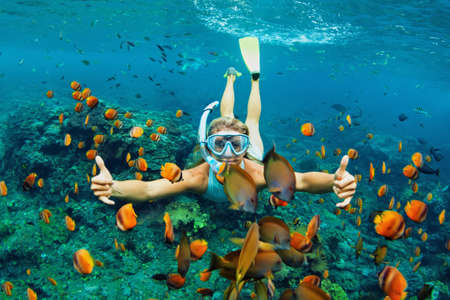 Happy family - girl in snorkeling mask dive underwater with tropical fishes in coral reef sea pool. Travel lifestyle, water sport outdoor adventure, swimming lessons on summer beach holiday with kids Standard-Bild - 98294866