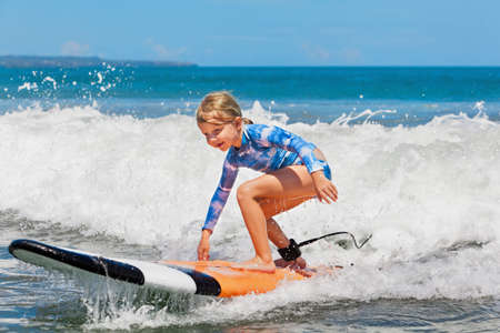 Happy baby girl - young surfer ride on surfboard with fun on sea waves. Active family lifestyle, kids outdoor water sport lessons and swimming activity in surf camp. Summer vacation with child.