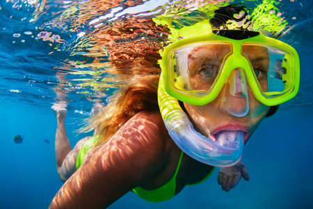 Happy girl in snorkeling mask dive underwater with tropical fishes in coral reef sea pool. Travel lifestyle, water sports, outdoor adventure, swimming lessons on family summer beach holiday with kids Stock Photo - 100318397