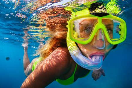 Glückliches Mädchen in der Schnorchelmaske tauchen unter Wasser mit tropischen Fischen im Korallenriff-Meeresbecken. Reiselebensstil, Wassersport, Abenteuer im Freien, Schwimmunterricht im Familiensommer-Strandurlaub mit Kindern