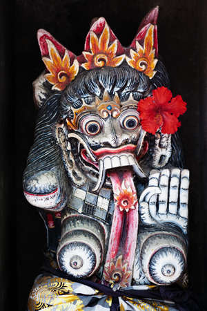 Old figure of traditional Balinese hindu spirit Rangda on wall of village temple at Bali island. Decorated by red flower for religious festival at Galungan holiday. Art, culture of Indonesian people.