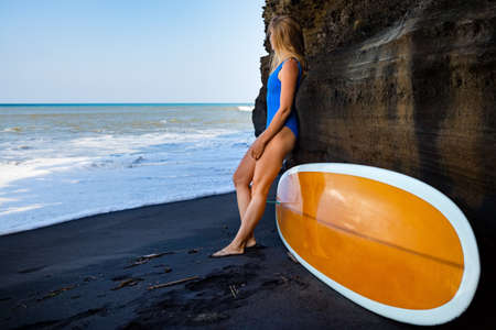 Girl in bikini with surfboard stand by cliff on black sand beach. Surfer woman look at sea surf and breaking waves. Active people in sport adventure camp, extreme activity on summer family vacation 写真素材