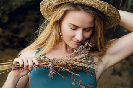 Young beautiful hipster woman in straw hat hold in hands bouquet of dried wild flowers. Happy romantic girl walk on tropical sea beach. Travel lifestyle, summer vacation accessories trend - boho style Stock Photo